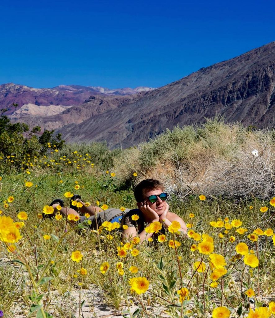 Ben Rubinoff laying in a field of wildflowers with mountains in the background